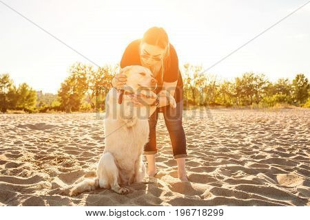 Young female training labrador retriever dog on the beach at sunset. White labrador retriever with a young woman. Sun flare