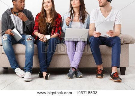 Young diverse students, people listen to music with gadgets, sitting together on couch indoors. Modern education.