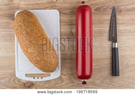 Sausage In Shell From Polyethylene, Knife, Bread On Cutting Board