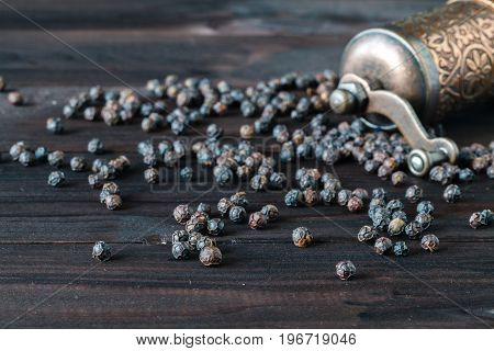 Old Pepper Mill And Peppercorns On Wooden Background