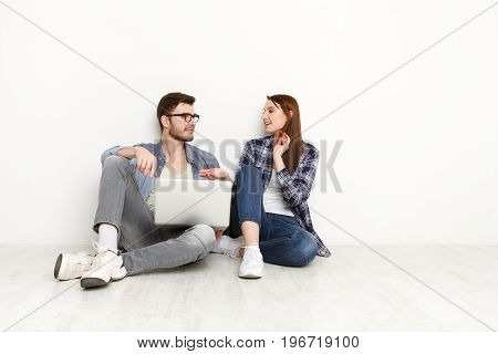 Online order. Couple shopping on laptop at food delivery while sitting on floor at new apartment, white background