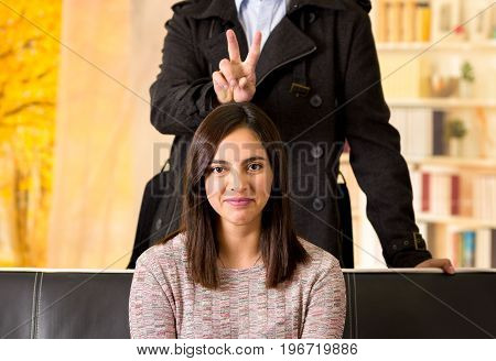 Beautiful young couple in love in st valentines day, man doing a sign over his girlfriend head in a blurred background.