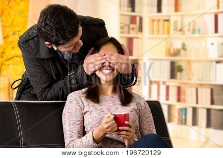 Beautiful young couple in love, boyfriend is covering the eyes of his girfriend in a office background.