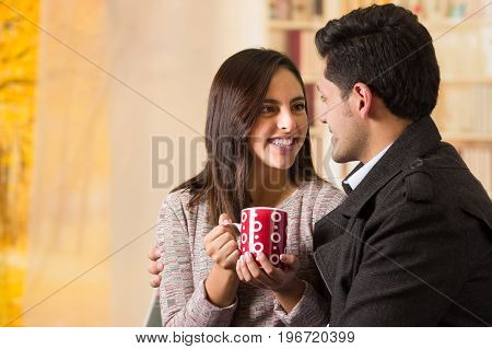 Beautiful young couple in love in st valentines day, holding a cup of coffe looking each other in a blurred background.
