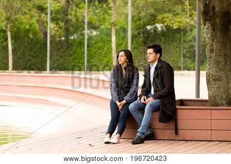 Beautiful young couple in love in st valentines day sitting in a park.