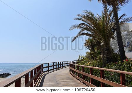 People walk near the beach on a wooden path