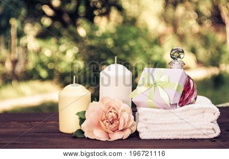 A pile of white soft towels fragrant oil roses and candles on a blurred green background. Spa concept. Vintage tinting