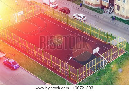 Basketball court in the courtyard of residential buildings, top view in sunny weather