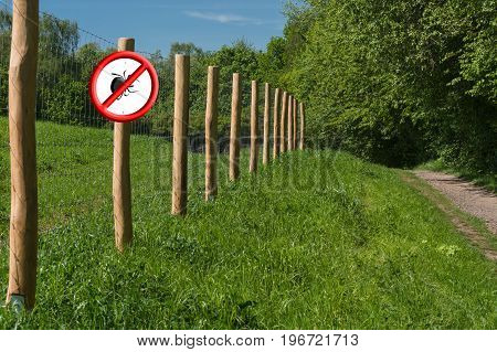 Red shield with crossed out ticks symbol on a fence post in front of a green meadow. Concept Ticks free zone
