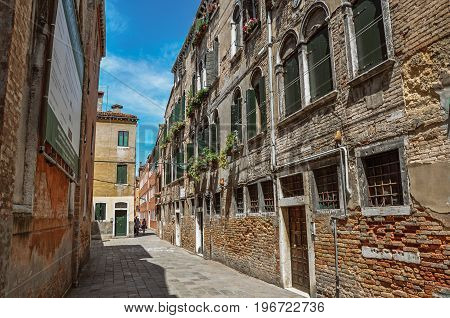 Venice, Italy - May 09, 2013. View of old buildings in an alley with blue sky in the city center of Venice, the historic and amazing marine city. Located in Veneto region, northern Italy