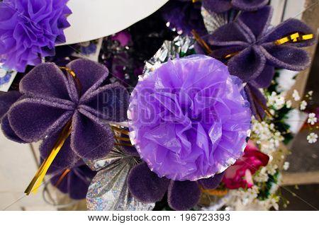 QUITO, ECUADOR- MAY 23, 2017: Close up of purple plastic flower located in cemetery of San Antonio de Pichincha in Quito city, Ecuador.
