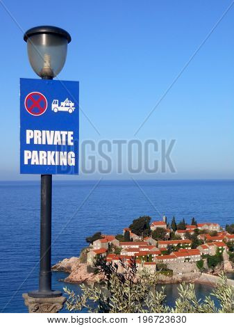 Parking sign and street lamp on the cliff over the little town on the seaside