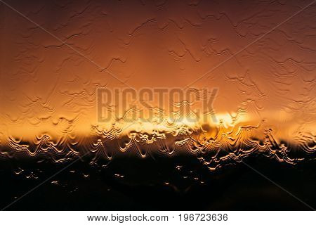 Water flows through the glass on the background of the sunset