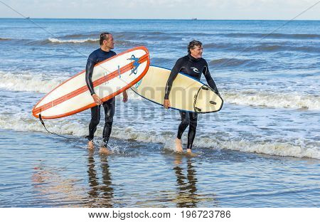 Kijkduin beach The Hague the Netherlands - 1 October 2016: middle aged men with surf boads walking through surf