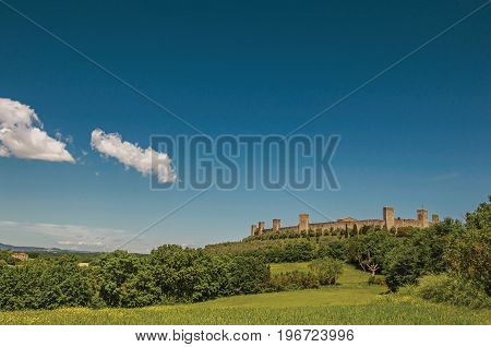 View of the stone walls of the hamlet of Monteriggioni on top of hill and surrounded by trees. A medieval fortress, surrounded by walls at the top of a hill near Siena. Located in the Tuscany region