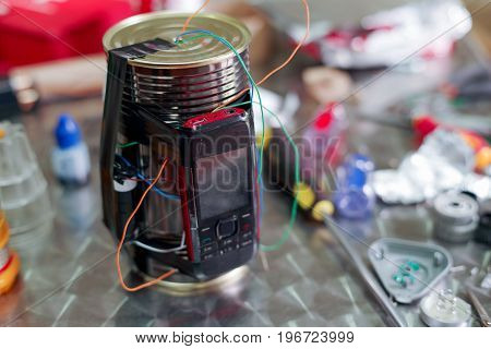 Homemade bomb with a cellphone timer, on a blurred background.