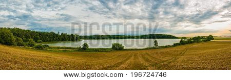 Beautiful peaceful place with nice clean lake, forest and field. Sunset on summer, panoramatic view.