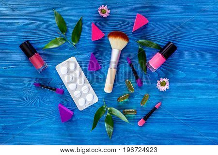 Contents of wonam's beauty bag on blue table background top view.