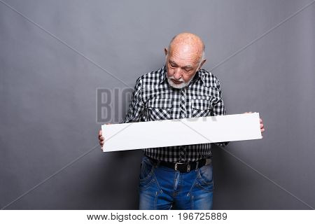 Senior man with blank white board. Mature male looking at advertising sheet, copy space