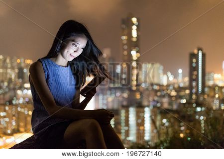 Woman reading on cellphone at night