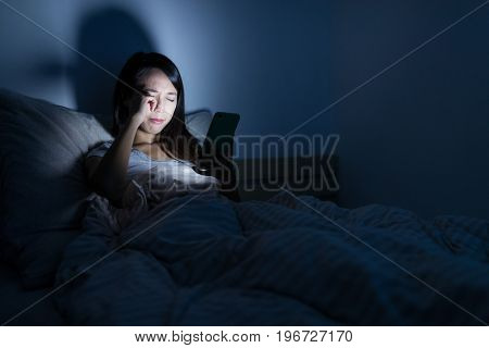 Woman feeling eye pain with using mobile phone at night