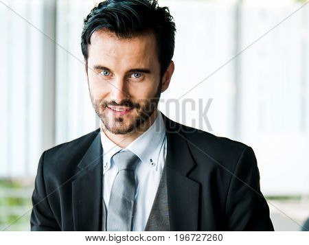 Portrait businessman smart confident and handsome with blue eyes and mustache in a formal attire or business suit and a grey necktie. He is in a relaxed period during an office montly meeting