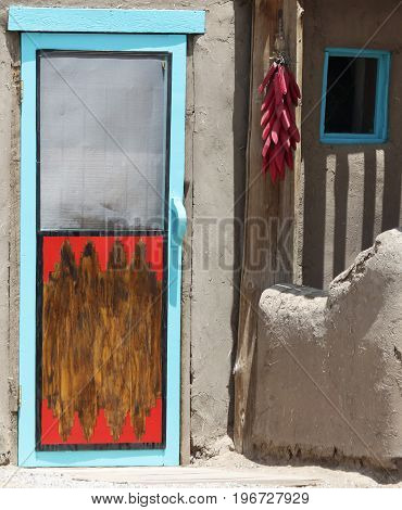 A String of Red Chili Peppers Hung Outside a Wooden Red and Blue Door of a Native American Pueblo