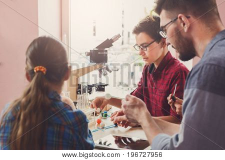 Stem education. Teenagers with teacher making chemical experiment in laboratory with reagents and microscope. Early development concept