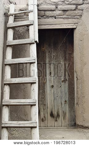 A Ladder Standing Outside a Wooden Door of a Native American Pueblo