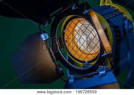 A spotlight with a Fresnel lens and a halogen lamp. Equipment for photographing and filming in the interior. Close-up.