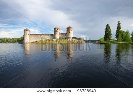Kyurensalmi strait and medieval fortress of Olanvinlinn in the cloudy July afternoon. Savonlinna, Finland