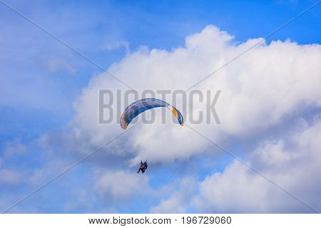 Lugano, Switzerland - 12 October, 2016: two persons flying with a paraglider in the blue sky with white clouds. A paraglider is a lightweight, free-flying, foot-launched glider aircraft with no rigid primary structure.