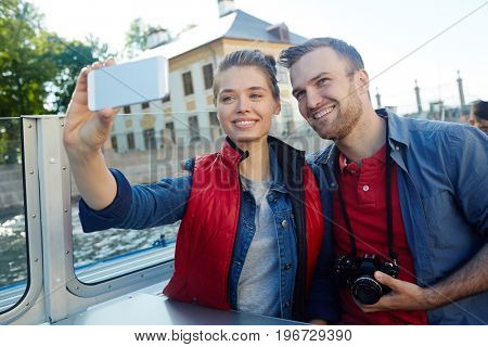 Affectionate lovers making selfie during cruise adventure