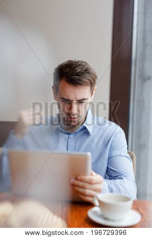 Young broker with touchpad reading online information