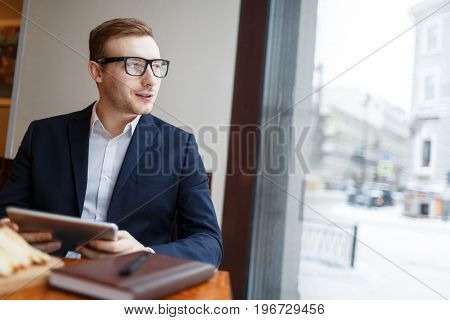 Confident businessman with touchpad looking through window