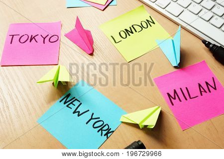 Traveling concept. Sticks with names Tokyo, London, Milan, New York and paper planes.