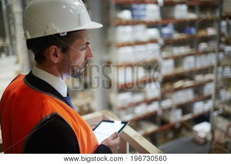 Side view portrait of warehouse supervisor looking down from balcony at tall racks with packed goods holding digital tablet in hand