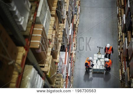 Above view of people working in large warehouse, counting goods on moving cart between shelves with packed boxes