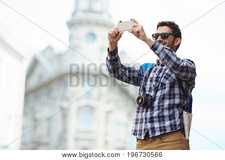 Portrait of modern young tourist taking selfie photo  in street of old city on solo trip in Europe