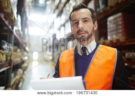 Portrait of warehouse supervisor  looking at camera holding note pad while doing inventory of stock
