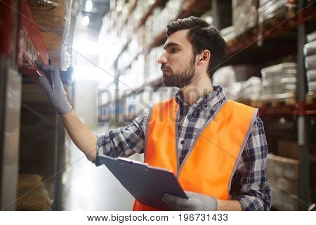 Side view portrait of bearded warehouse worker checking labels on shelves with goods while doing inventory controlWarehouse worker reviewing goods