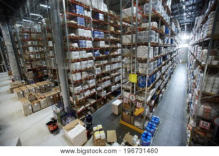 Wide angle shot of warehouse interior with rows of shelves and racks