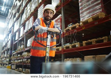 Portrait of cheerful warehouse loader at work, pushing moving cart and looking at camera