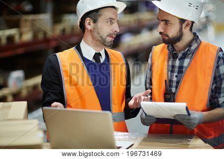 Portrait of warehouse manager talking to loader while doing stocktaking using laptop to comply list of goods