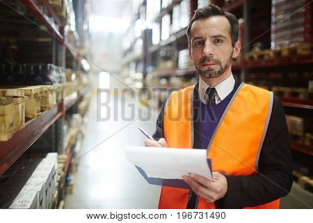 Portrait of warehouse manager looking at camera holding clipboard while doing inventory of stock