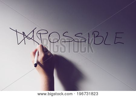 Businesswoman changing word Impossible to Possible on office whiteboard with marker felt pen selective focus