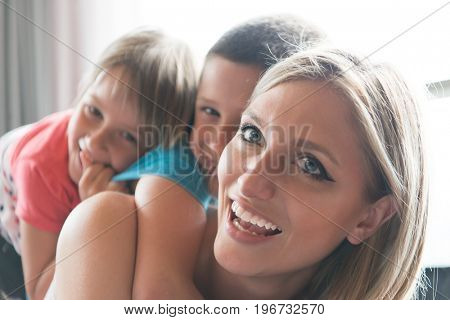 Happy Mother with kids having fun on the floor at home