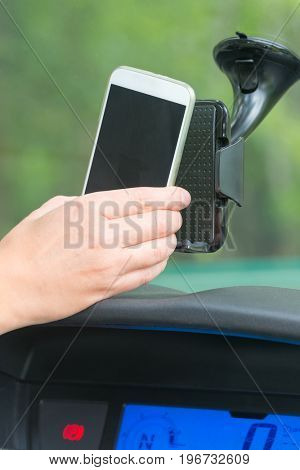 Hand inserting smart phone into the car holder and adjusting clamps