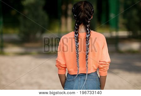Girl stands with her back on her head hairstyle made of blue pigtails, kanekalon.