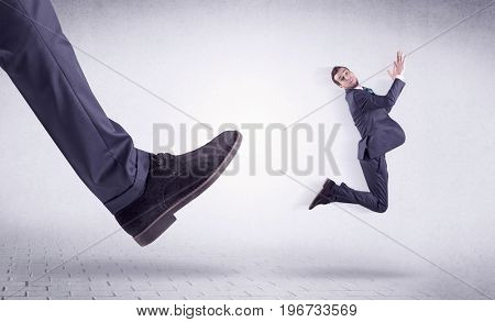 Small young businessman kicked out by a big black shoe